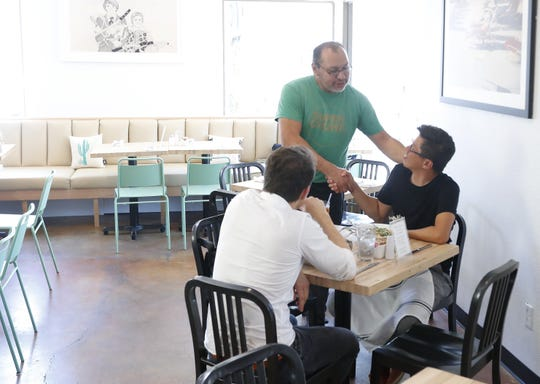 Sergio Velador shakes the hand of Thamarit Suchart inside of Super Chunk Bakery and New Wave Market in Scottsdale, Ariz. on July 25, 2019.
