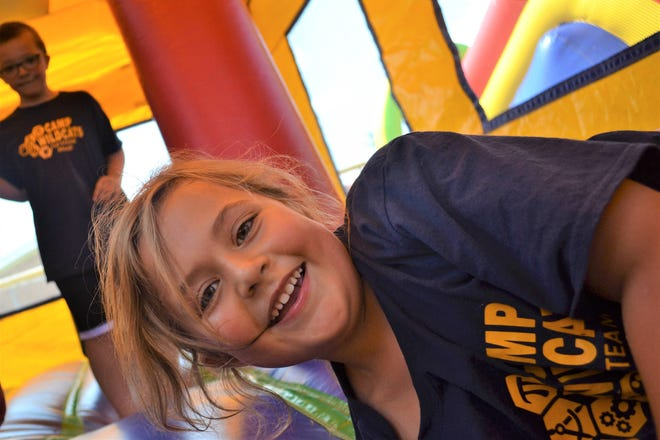 Campers have fun in the bouncy houses at Camp Wildcats on Friday.