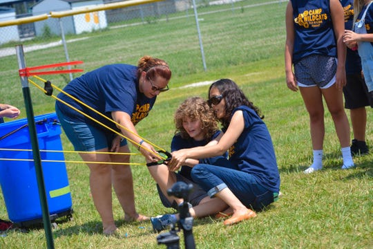 Special education director Carla Smith, left, and paraprofessional Lydia Kigar, right, help Evie Lockwood aim a giant slingshot loaded with a water balloon.