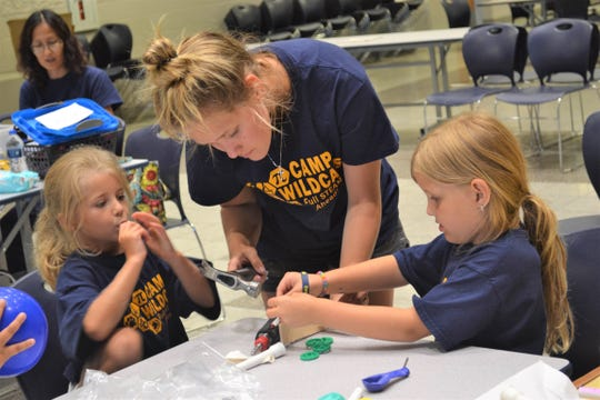 Woodmore senior Syndi Buhrow helps campers build race cars on Friday. Buhrow said she enjoyed volunteering at the camp with the younger students.