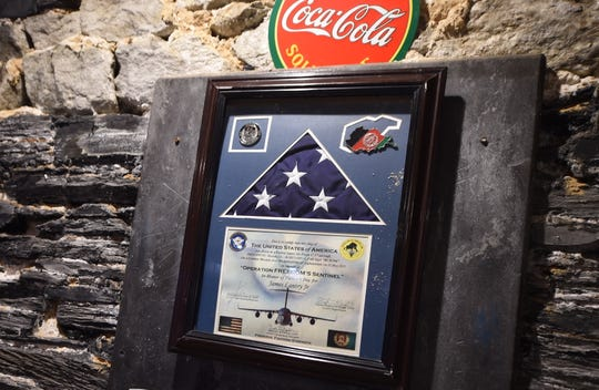"A frame American flag and commemorative plague hang honoring veteran James Lantry Jr. in the basement of Delta Pizza. The restaurant has been nominated as a 2019 finalist for Reader's Digest's ""Nicest Place in America"" award."