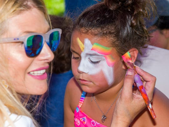 Heidi Figueroa of Artistas paints a unicorn on the face of Claudia Mendoza, 7, of Fernley.