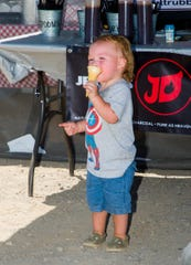 Walker Zaldivar, 1, of Fernley cools off and eats an ice cream cone in the shade in front of the Butt Rub'n BBQ food truck.