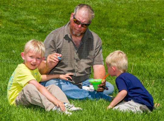 David Cogley of Fernley shares a snow cone with his sons, Teddy, 5, left, and Gabriel, 3.