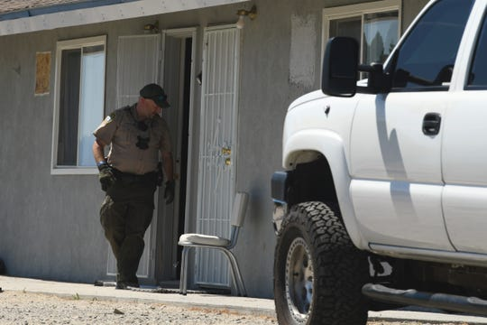 A Mineral County sheriff's deputy exits an apartment in Walker Lake, Nevada, associated with Santino William Legan, 19.