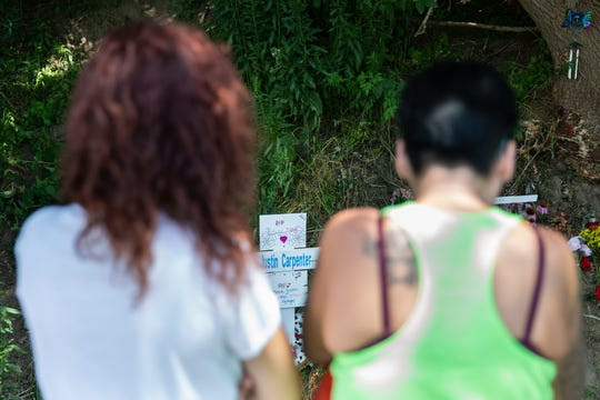 Latoya Curry, left, and Amanda Marriott look at a cross with Justin Carpenter's name on it that was placed at the scene of the car accident in which he was killed. Carpenter, 14, and three other teens were killed in the crash in Burns, New York, early Saturday morning.