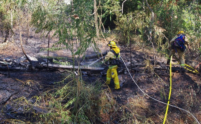Firefighters work on a fire that burned about two-thirds of an acre in a gully about a quarter of a mile northwest of Lake Boulevard and Shasta Dam Boulevard on Sunday.
