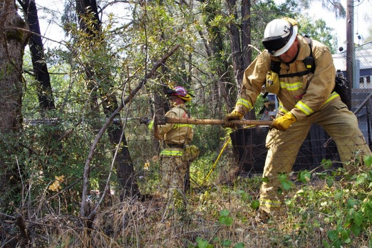 Firefighters work on a fire about a quarter-mile northwest of Shasta Dam Boulevard and Shasta Lake Boulevard on Sunday.