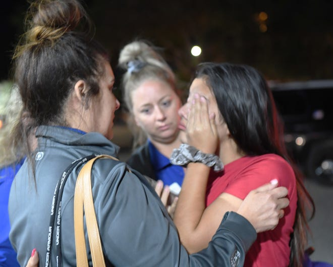People reunite with family members in  the parking lot of Gavilan College after a gunman shot into the crowd indiscriminately at the annual Gilroy Garlic Festival. July 29, 2019.