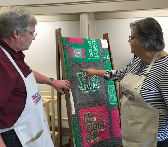 Phillip and Debbie Steinbach inspect a Wall Hawks quilt at Quilting Quarters, 2124 W. Beauregard Ave., on July 29, 2019. The couple's business will open on Thursday, Aug. 1.