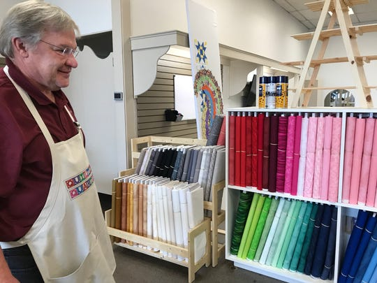 Phillip Steinbach looks over the wall of colorful fabrics at Quilting Quarters, 2124 W. Beauregard Ave., on July 29, 2019.
