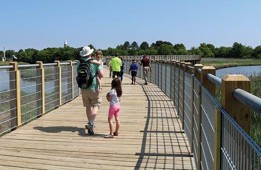 Visitors walk along the Waterwalk, a 2.25-mile linear park in Hampton, Virginia.