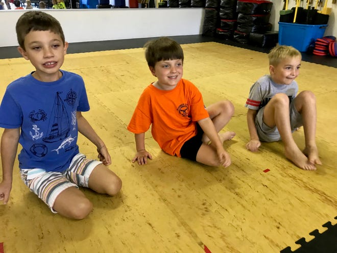 Nicolas Church-DiCiccio sits between two friends while celebrating his sixth birthday at Staunton's American Freestyle Karate on Saturday, July 27, 2019.
