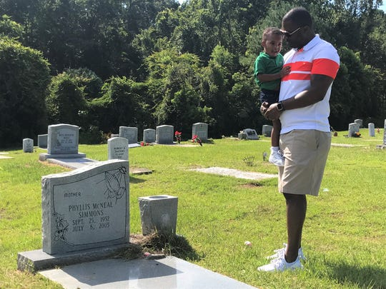 FAMU football head coach Willie Simmons visits the gravesite of his mother Phyllis McNeal Simmons with his son Wraylon in Quincy.