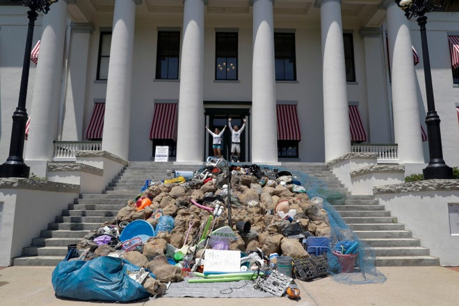 Plastic Symptoms Co-Founders Heather Bolint and Bryan Galvin stand atop the steps of the Florida Historic Capitol after two hours of unloading nearly 3,000 pounds of garbage the pair collected from the ocean along Florida's coastline onto the steps. They brought the load to the Capitol Monday, July 29, 2019, to bring awareness to the harms of single-use plastics.