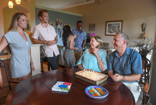 """Hannah Haislah (left), and her brother Josh Bartz, enjoy a moment with their parents Donna and John Bartz (seated on right), while celebrating their father's 52nd birthday a day early on Sunday, July 28, 2019, along with Hannah's husband Noah Haislah (background) and Josh's wife Taylor Bartz, at their parent's house south of Stuart in Martin County. Donna Bartz has been recently diagnosed with a genetic, aggressive form of lung cancer that spread to her bones, and is now in a wheelchair. """"Collectively, we're really proud of her,"""" Hannah Haislah said. """"It's been really tough the past seven months now, but she's pushing on every day, and each day brings new challenges but she just looks to God and family for support, so she's doing really well. We're really proud of her."""""""