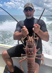 Alek Loudakis of Stuart and the 7-pound lobster which took off the tip of his left index finger.
