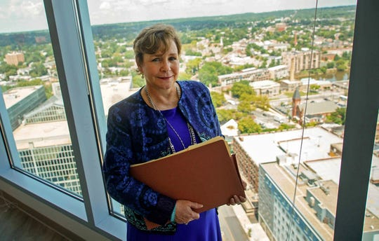 Gail Wagner, a paralegal at Connolly Gallagher, stands next to a window in the firm's new space that has a 360 view of Wilmington.