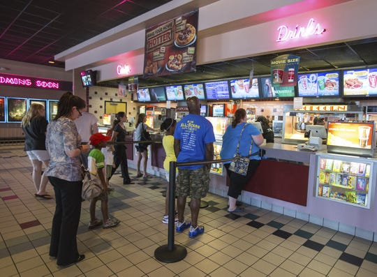 Moviegoers line up at the concession stands at the Regal Cinemas at People?s Plaza in Glasgow on a Wednesday in July 2013.