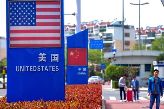 In this May 8, 2019, photo, people walk by a display boards featuring the U.S. and Chinese flags in a special trade zone in Qingdao in eastern China's Shandong province. A government spokesman says Chinese companies have expressed willingness to import U.S. farm goods as envoys prepare to meet next week for talks aimed at ending a tariff war.