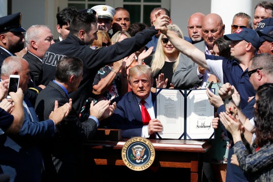 President Donald Trump holds up the signed H.R. 1327 bill, an act ensuring that a victims' compensation fund related to the Sept. 11 attacks never runs out of money, in the Rose Garden of the White House on July 29, 2019, in Washington.