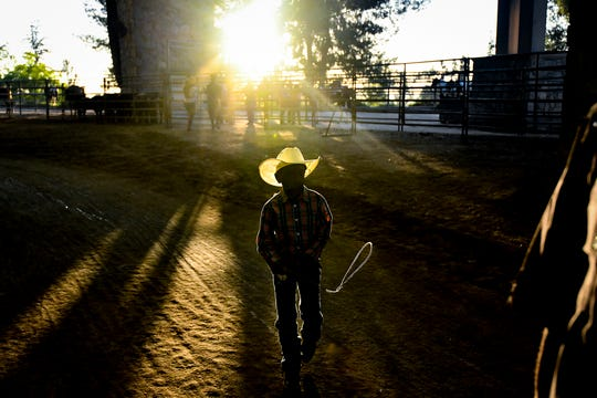 A young cowboy hangs out back stage at the Industry Hills Expo Center outdoor arena during the 35th annual Bill Pickett Rodeo on July 20, 2019 in City of Industry, California.