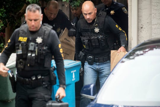 Police officers carry evidence bags from the family home of the suspected Gilroy Garlic Festival gunman in Gilroy, Calif.