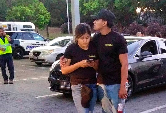 A young couple embrace at a parking lot after a shooting at the Gilroy Garlic Festival in Gilroy, Calif., Sunday, July 28, 2019. Several people were hospitalized Sunday after the shooting at the annual food festival in Northern California, a hospital spokeswoman said.