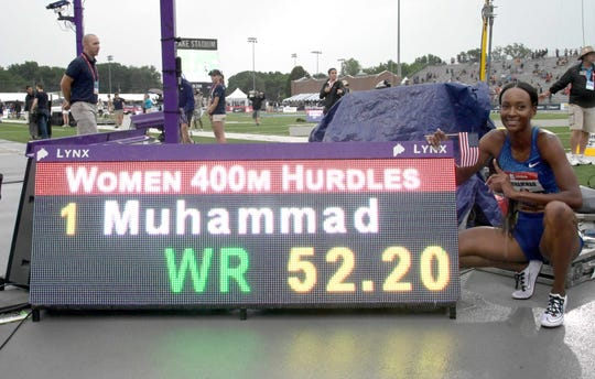 Dalilah Muhammad poses with scoreboard after winning setting a new world record in the 400-meter hurdles.