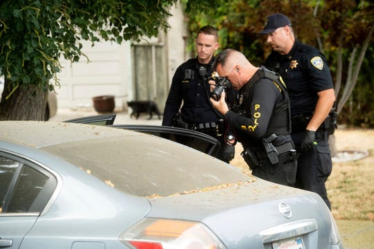 A police officer photographs a car outside the family home of Gilroy Garlic Festival gunman on July, 29, 2019, in Gilroy, Calif.