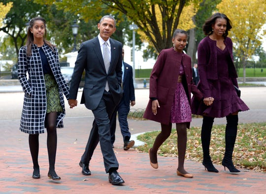 President Barack Obama walks with his wife Michelle Obama and two daughters Malia Obama and Sasha Obama through Lafayette Park to St John's Church to attend service Oct.  27, 2013 in Washington, DC.