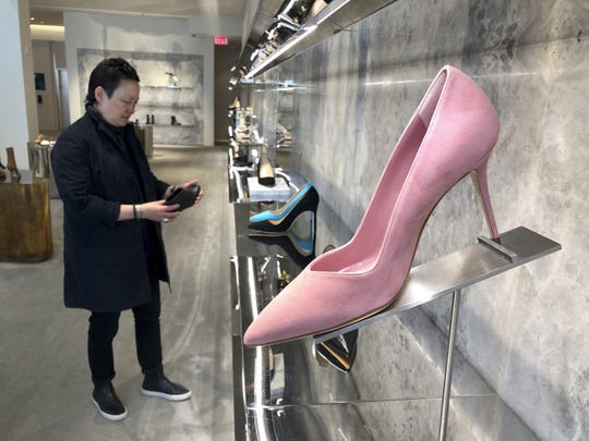"""Personal shopper and stylist Kat Yeh looks at shoes for a client in San Francisco. One of the fastest-growing job categories of the past decade has been in what economists call """"wealth work"""": Catering to the whims, desires and appetites of the wealthy."""