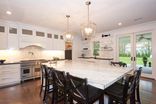The white sun-filled kitchen features a large island with calacatta marble countertops.