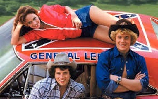 "The stars of ""The Dukes of Hazzard"" with the General Lee."