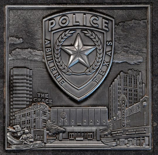 One of the stamped metal tiles inset into the lobby of the Abilene Police Department headquarters.