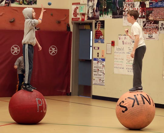 Benjamin Oleyar, 11, left, and Austin Hawks, 11, right, play catch as they balance on large balls during Circus Camp at Poulsbo Elementary School on Tuesday.