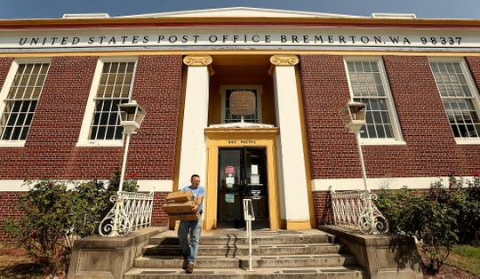 Steve Mastel, of Bremerton, exits the Bremerton Post Office on Pacific Avenue with a stack of packages on Tuesday. U.S. Rep. Derek Kilmer introduced a bill to rename the Bremerton Post Office to honor John Henry Turpin, one of the first black Navy chief petty officers.