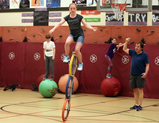 Moira Johnson, 13, rides three-wheeled unicycle through the gym under the watchful eye of Bob Webb, at right, during Circus Camp at Poulsbo Elementary School on Tuesday.