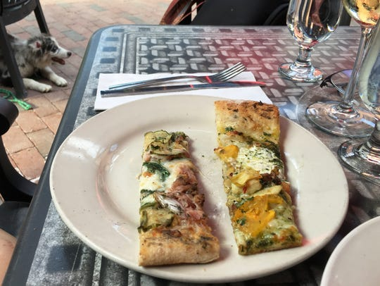 Two slices from the daily specials at American Flatbread in Burlington await a diner Monday, July 29, 2019. On the left: braised/smoked pork with cheddar, sweet & spicy pickles, arugula, and house-made maple mustard. The slice on the right features arugula pesto,  fresh tomatoes, mozzarella, grilled artichoke and green olives.