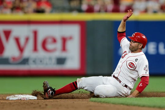 Cincinnati Reds first baseman Joey Votto (19) advances to second base on a single by Cincinnati Reds third baseman Eugenio Suarez (7) (not pictured) in the fifth inning of an MLB baseball game against the Pittsburgh Pirates, Monday, July 29, 2019, at Great American Ball Park in Cincinnati.