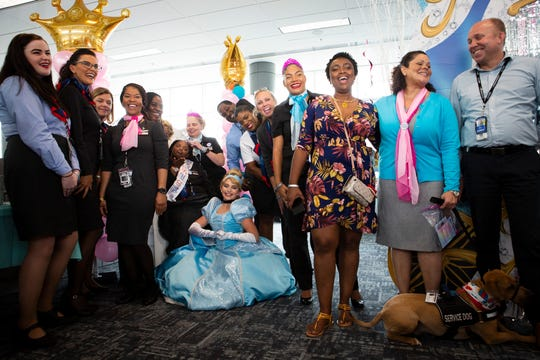 "Shantell ""Shannie"" Pooser, a self-proclaimed princess and teenager with Down syndrome, poses for a picture with her mother (wearing a floral dress), Cinderella and workers for American Airlines. Pooser arrived to a special surprise celebration on Monday, July 29, at the Cincinnati/Northern Kentucky International Airport (CVG). Po"