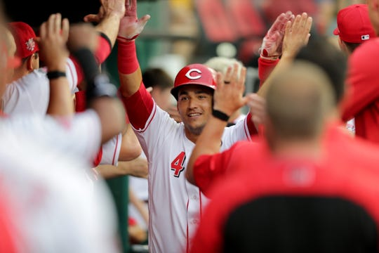 Cincinnati Reds shortstop Jose Iglesias (4), center, is congratulated in the dugout after hitting a grand slam home run in the second inning of an MLB baseball game against the Pittsburgh Pirates, Monday, July 29, 2019, at Great American Ball Park in Cincinnati.