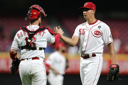 Cincinnati Reds relief pitcher Robert Stephenson (55) shakes hands with Cincinnati Reds catcher Tucker Barnhart (16) at the end of the game in the ninth inning of an MLB baseball game against the Pittsburgh Pirates, Monday, July 29, 2019, at Great American Ball Park in Cincinnati.