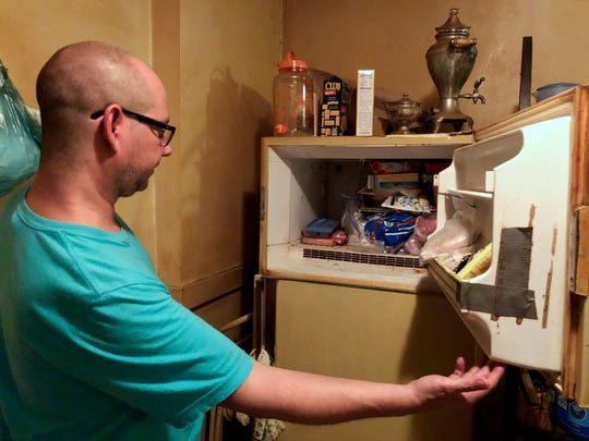 In this Monday, July 29, 2019 photo, Adam Smith peers into his mother's freezer in St. Louis, where he found the remains of an infant wrapped in a box she kept there for more than 40 years.