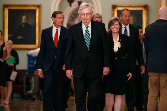 Senate Majority Leader Mitch McConnell of Ky., center, walks with Sen. John Barrasso, R-Wyo., left, Sen. Joni Ernst, R-Iowa, and Republican Conference Chair Sen. John Thune, R-S.D., walks to speak to the media, Tuesday, July 30, 2019, after their weekly policy luncheon on Capitol Hill in Washington.