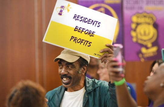 An SEIU home health care worker holds a sign as workers demand accountability and push for policies to address wages and safe staffing for nursing home workers.
