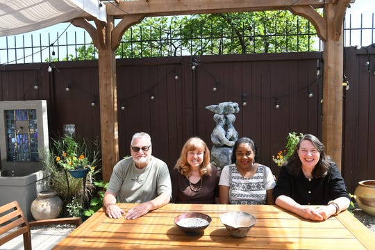From left, Harry Swanson of Detroit, Rosi Triano of Grosse Pointe Farms, Michelle Dinwiddie Segue and Aislinn Scofield, both of Detroit, sit in the new courtyard at Pewabic Pottery in Detroit on July 24, 2019. They are members of the Eastside Mudslingers.