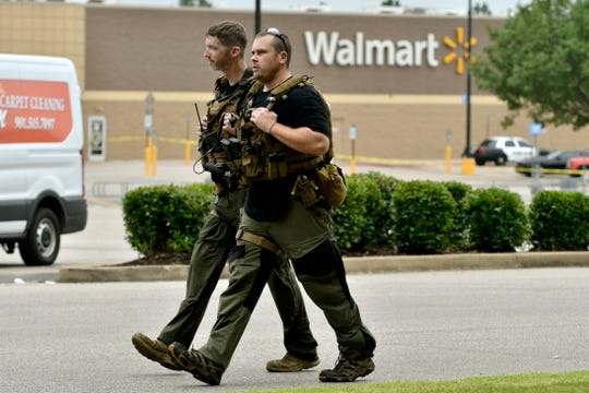 Sheriff deputies walk through the parking lot after a shooting at a Walmart store Tuesday, July 30, 2019 in Southaven, Miss. A gunman fatally shot two people and wounded a police officer before he was shot and arrested Tuesday at the Walmart in northern Mississippi, authorities said.