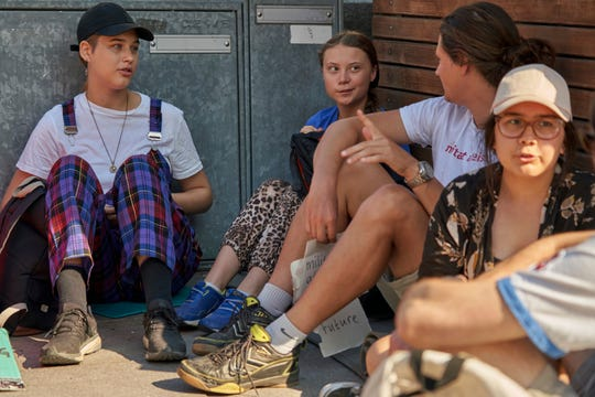 Greta Thunberg, third from right, sits with fellow students outside Swedish parliament in Stockholm on July 26.