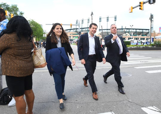 Democratic presidential candidate Pete Buttigieg, center, crosses Woodward by Comerica Park for the debates at the Fox Theatre.